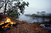 Zambia. Riverscape at dawn with log campfire burning in the foreground.