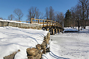 Old North Bridge at Minute Man National Historical Park in Concord, Massachusetts during the winter months. This footbridge spans the Concord River, and it is the site of a Revolutionary War Battlefield (on April 19, 1775, battle of Concord, which marked the beginning of the American Revolutionary War).
