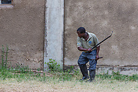 Tanzania. Serengeti. Laborer Cutting Grass with a Machete.