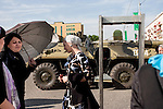 Women wait to go through a metal detector at one of the entrances to downtown Grozny just before the Victory Day parade on May 9, 2010. An armoured personal carrier is parked outside. Grozny, Chechnya, Russia, 2010