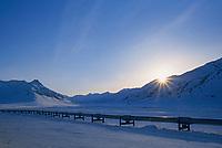 Sun sets behind the winter Brooks mountains, Trans Alaska Oil Pipeline, Alaska.