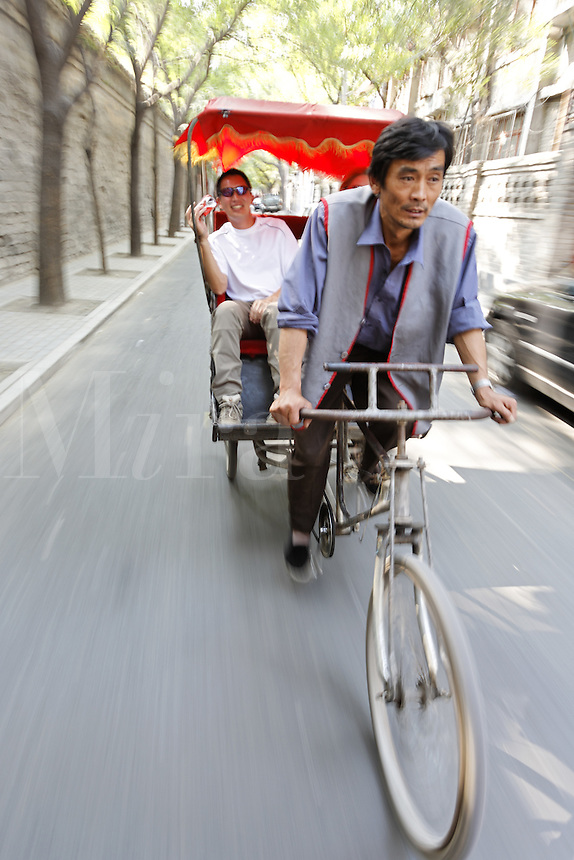 A pedicab driver gives a tourist a rickshaw ride through a Beijing hutong, Beijing, China, Asia