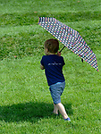 A toddler takes a walk in the summe sun.