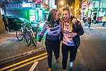 """© Joel Goodman - 07973 332324 . 15/12/2017. Manchester, UK. A woman wearing a Christmas jumper that reads """" You're on my naughty list """" walks with a friend through Manchester's """" Gay Village """" . Revellers out in Manchester City Centre overnight during """" Mad Friday """" , named for historically being one of the busiest nights of the year for the emergency services in the UK . Photo credit : Joel Goodman"""