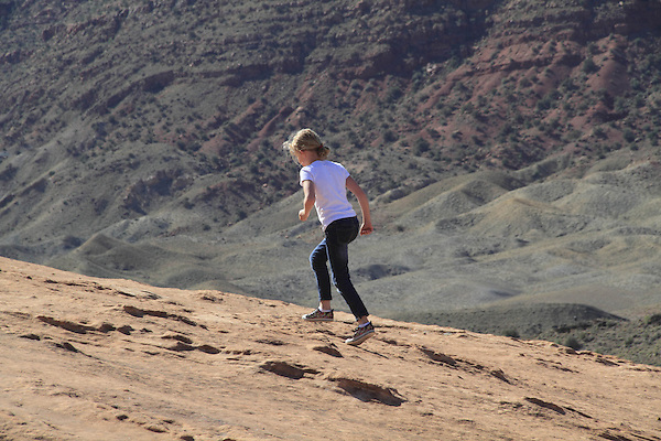 Girl running uphill on slickrock in Arches National Park, Moab, Utah, USA. .  John offers private photo tours in Arches National Park and throughout Utah and Colorado. Year-round.