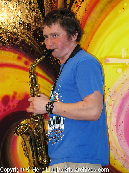 Marshall Farrell plays saxophone at an Airport Muse art exhibit at the Petaluma Municipal Airport, Petaluma, Sonoma County, California