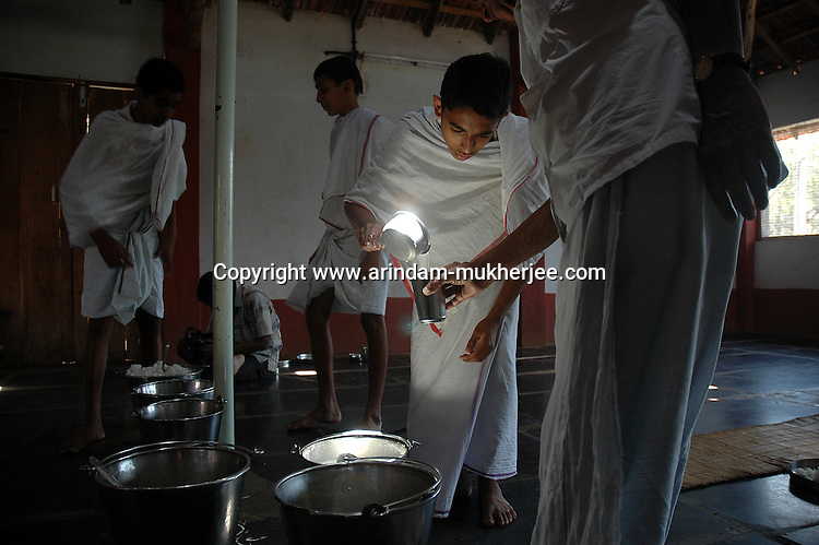 A Student of Om Shantidhama serving milk to one of the teacher.  Om Shantidhama is a residential vedic school for boys. Nestled among the confluence of hills, forest and rivers - Om Shanti Dhama is a world removed from the maddeningly fast and often chaotic urban India. Students from allover the country are selected to take part in its Vedic and free education system. What is unique about this institute is that they have blended the traditional and modern education system. Here computer and science is taught with the same passion as the Vedas and Shastras, helping the students to grow spiritually as well as earn a living. Bonding with the nature and animal world is a mandatory part of the institute's curriculum. Karnataka, India. Arindam Mukherjee
