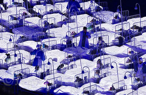 """27 JUL 2012 - LONDON, GBR - A doctor and nurses walk between the beds of sleeping children during the """"Second To The Right, And Straight On Till Morning"""" section of the Opening Ceremony of the London 2012 Olympic Games in the Olympic Stadium in the Olympic Park, Stratford, London, Great Britain .(PHOTO (C) 2012 NIGEL FARROW)"""
