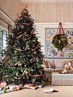 The comfortable living room is decorated for Christmas, with an impressive fir. A wreath hangs from the cornice above the sofa and the ottoman has a deep fringe.