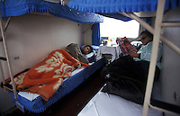 Passengers rest in the couchette on the Beijing to Hong Kong long-distance train, Beijing, China.