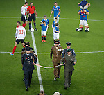 Armed forces carry a giant poppy from the centre circle prior to kick-off