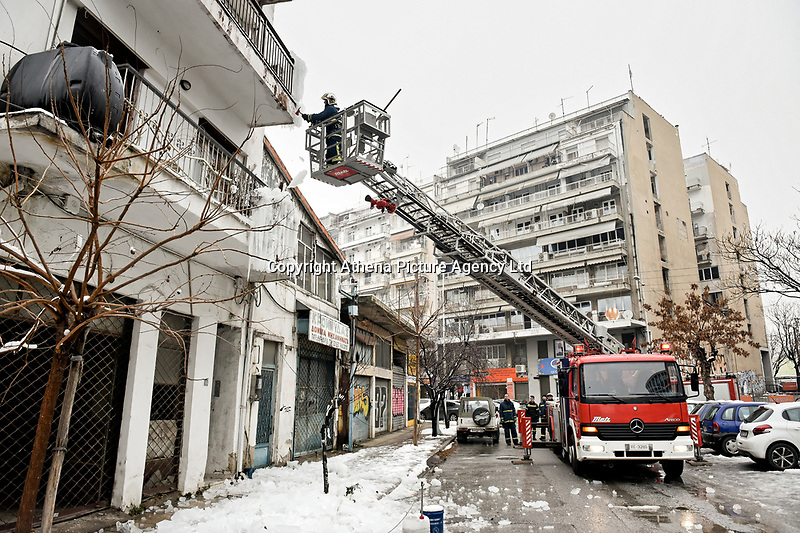 Pictured: A fireman on a cherry picker hacks off ice from the front of a block of flats in Salonica, northern Greece. Thursday 10 January 2019<br /> Re: A fire engine had to be called to remove icicles that formed at the front of a block of flats when a water pipe on top of the building burst in the city of Salonica, northern Greece.