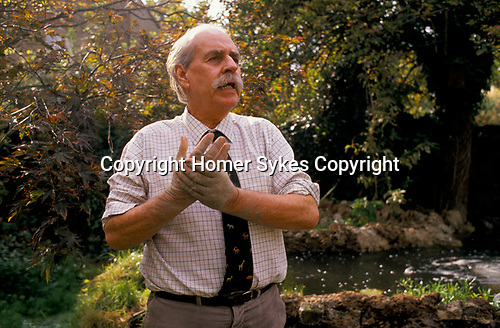 Bob Astles, Idi Amin's right hand man and fixer, Kenilworth Avenue, Wimbledon,  London 1990. His water garden large pond feature he is building. 1990 UK