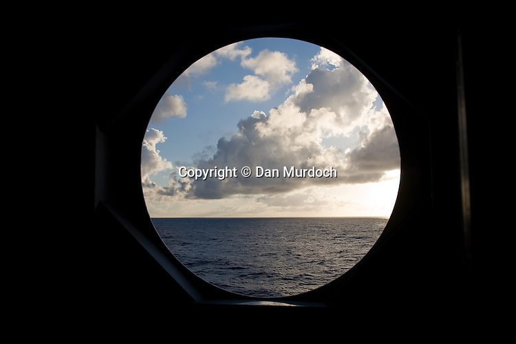Beautiful clouds peaking through a port hole on a cruise ship.