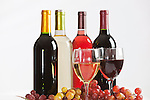 Four different wine bottles, two glasses of wine, and grapes.  Red, white, rose, zinfandel.  White background.