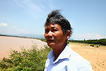 """Nguyen Tan Hoa, 55, stands on the bank of the Vu Gia River across from the spot where Sgt. Michael Frank Flynn was killed in April, 1965 outside the village of Tam Hoa, Vietnam. Flynn was the team leader for Charlie 2-2-4 under the Combined Action Program, which sent small units of Marines into villages in South Vietnam to train local militia and keep Viet Cong guerrillas out. As a boy, Nguyen spent much of his free time hanging out with the Marines, who adopted him into the unit. It was the most profound experience of his life, and he still refers to himself proudly as a Marine. """"When the Americans left in '75, I really felt like I was the last G.I. in Vietnam,"""" he says. May 12, 2012."""