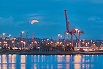 Full moon Supermoon or Perigee Moon rises over Seattle, Washington, Harbor Island and Container Terminals, Elliott Bay.  Container craines, full moon, Beacon Hill, Harbor Island, Port of Seattle.