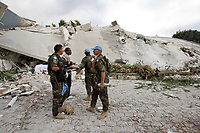 A Haitian man and MINUSTAH peacekeepers plan a way to access the interior of the Montana hotel that collapsed after an earthquake measuring 7 plus on the Richter scale rocked Port au Prince Haiti just before 5 pm yesterday, January 12, 2009.