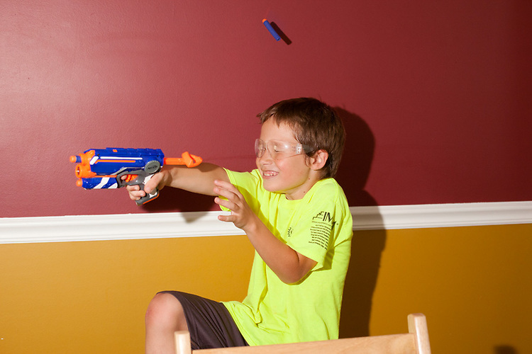 My older son takes a direct hit during a Nerf gun war inside our house.