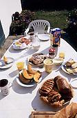 Pendruc, Britanny, France. Breakfast table with pastries, bread, croissants, pain au chocolat, melon, cheese, orange juice.