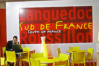 Poster with Languedoc Roussillon Sud de France South of France, the new slogan for the wines from this region, on a red and yellow poster on a wall in a cafe at the launch of the branding at the Vinisud trade fair in Montpellier, France. A man sitting at a table working on a laptop computer