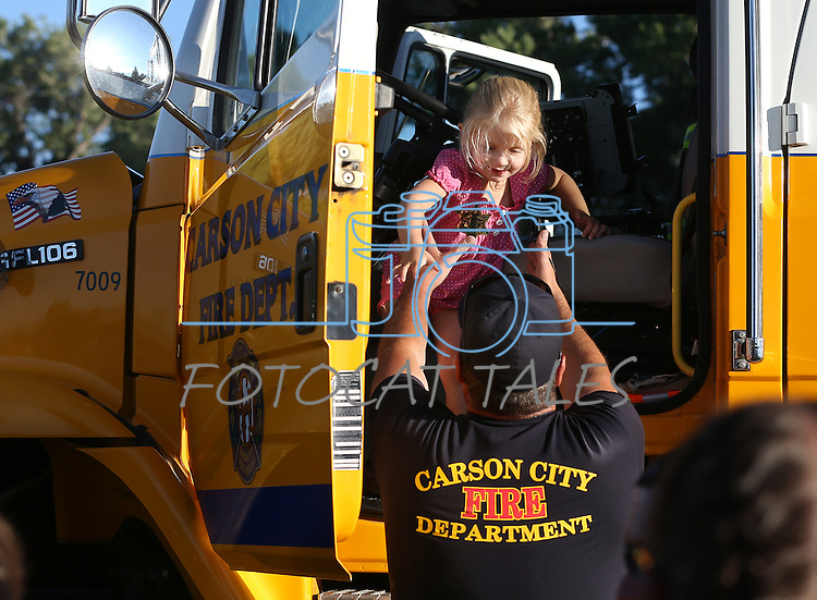 Jolyne Craig, 4, checks out a Carson City Fire Department engine during the 14th annual National Night Out in Carson City, Nev., on Tuesday, Aug. 2, 2016. <br />Photo by Cathleen Allison