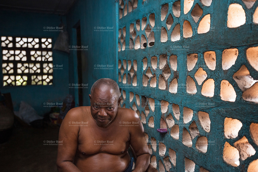 Nigeria. Enugu State. Agbani. Igbo elderly man. A shirtless overweight man seats at home alone in the shade. 14.07.19 © 2019 Didier Ruef