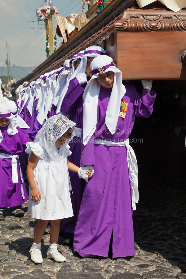 Antigua, Guatemala.  Little Sister Accompanies her Brother as he Carries a Float in a Religious Procession during Holy Week, La Semana Santa.