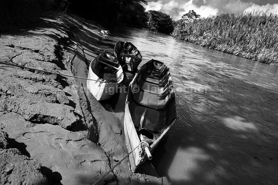 Boats of Colombian sand miners are seen tied up at the bank of the river La Vieja in Cartago, Colombia, 10 December 2013. Artisanal (unmechanised) sand mining is an ancient mining technique used to obtain sand for construction purposes. Depending on the natural conditions (strength of the stream, depth of the river etc.), together with the sand miners' physical condition, the material is extracted in metal buckets, either by standing on the river bottom and searching for sand by feet, or, diving up to 3-5 meters deep using a wooden plank with steps. In spite of the physically demanding work, a sand miner's daily salary does not exceed 15-20 US dollars. However, the sand miners are very proud of their profession, valuing their work freedom above all, and usually, as long as their health and strength permit, they keep facing the river stream.