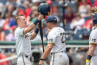 Michigan Wolverines first baseman Jimmy Kerr (15) is greeted by head coach Erik Bakich (23) during Game 11 of the NCAA College World Series against the Texas Tech Red Raiders on June 21, 2019 at TD Ameritrade Park in Omaha, Nebraska. Michigan defeated Texas Tech 15-3 and is headed to the CWS Finals. (Andrew Woolley/Four Seam Images)