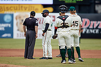 Greensboro Grasshoppers manager Kieran Mattison (24) discusses a call with umpire Greg Roemer during the game against the Rome Braves at First National Bank Field on May 16, 2021 in Greensboro, North Carolina. (Brian Westerholt/Four Seam Images)