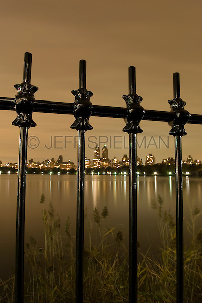 AVAILABLE FROM JEFF AS A FINE ART PRINT.<br /> <br /> AVAILABLE FROM JEFF FOR COMMERCIAL AND EDITORIAL LICENSING.<br /> <br /> Manhattan's Upper West Side on an Overcast Night, Viewed Thru Cast Iron Fence Surrounding the Central Park Reservoir, New York City, New York State, USA