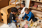 Education preschool 3 year olds two boys and a girl playing with doll house dolls and furniture