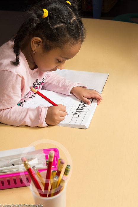 Education Preschool 4 year olds start of day sign in activity girl writing her name with pencil using tripod grip
