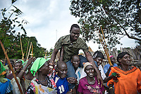 Joseph Gatyoung Khan is carried through his village as friends and relatives celebrate his homecoming. Joseph is a Lost Boy. He was among the thousands who fled Sudan during the civil war, and after living in the United States, he is returning for the first time in 22 years. Many Sudanese are returning home, mainly to participate in the upcoming referendum in January 2011 when South Sudan will vote on its independence..