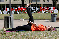 Thalita Da Silva Hotz, a graduate assistant, listens to yoga teacher Philip Shepherd, with the Department of University Recreation, Friday, April 30, 2021, as she participates in a stretching yoga session during the Dead Day Bash on the campus of the University of Arkansas in Fayetteville. Hosted by University Housing the event include lawn games, a hot dog grill out, a study tips scavenger hunt and other activities. Check out nwaonline.com/210501Daily/ and nwadg.com/photos for a photo gallery.<br /> (NWA Democrat-Gazette/David Gottschalk)