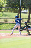Los Angeles Dodgers outfielder Brayan Rodriguez (99) at bat in front of catcher Cesare Astorri (12) during an Instructional League game against the Oakland Athletics at Camelback Ranch on September 27, 2018 in Glendale, Arizona. (Zachary Lucy/Four Seam Images)