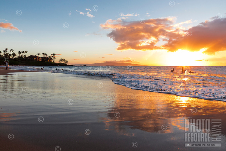 A family enjoys the waters of Wailea Beach, Maui, at sunset.