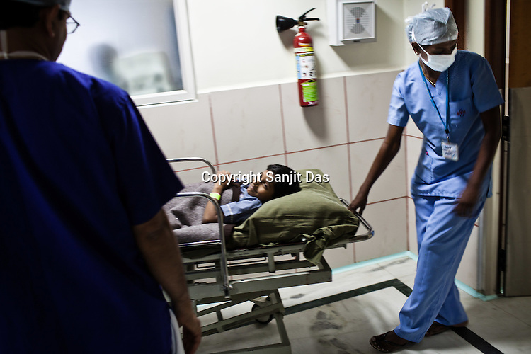 A young boy is taken to the operation theatre on the stretcher at the Narayana Hrudayalaya in Bangalore, Karnataka, India. Photo: Sanjit Das/Panos