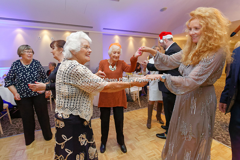 Pictured: Lottery winner Karen Willett (R) dances with one of the guests. Wednesday 28 November 2018<br /> Re: National Lottery millionaires from south Wales and the south west of England have hosted a glitzy Rat Pack-inspired Christmas party for an older people's music group at The Bear Hotel in Cowbridge, Wales, UK.