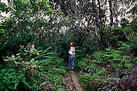Woman standing on man made boardwalk in the pristine Kamakou rainforest trail led by the Nature Conservancy