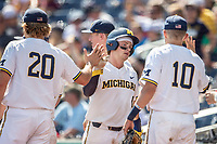 Michigan Wolverines catcher Joe Donovan (0) is greeted by his teammates after scoring during Game 11 of the NCAA College World Series against the Texas Tech Red Raiders on June 21, 2019 at TD Ameritrade Park in Omaha, Nebraska. Michigan defeated Texas Tech 15-3 and is headed to the CWS Finals. (Andrew Woolley/Four Seam Images)