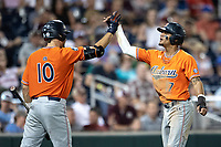 Auburn Tigers shortstop Will Holland (17) is greeted by teammate Edouard Julien (10) during Game 4 of the NCAA College World Series against the Mississippi State Bulldogs on June 16, 2019 at TD Ameritrade Park in Omaha, Nebraska. Mississippi State defeated Auburn 5-4. (Andrew Woolley/Four Seam Images)