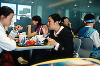 China. Province of Beijing. Beijing. A couple of young woman eat at lunch junk food - hamburger and french fries and  drink soft beverages in a fast food Mac Donald restaurant . © 2004 Didier Ruef