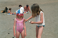 Young girl putting sun cream on her younger sister.