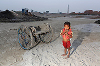A child in the grounds of a brick factory, in the Malancha district of eastern Kolkata. As their parents work nearby, children often play in the area, exposing them to harmful materials and waste produced in the industrial process. India. November, 2013