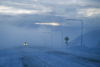 Vehicle travels through high winds and blowing snow over the Steese Highway, Eagle Summit, Alaska