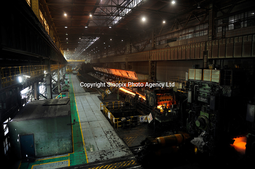 Molten hot plate steel being rolled at Shanghai Baosteel factory. Baosteel is the largest Chinese iron and steel conglomerate. It is a state-owned enterprise, headquartered in Shanghai..