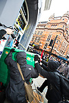 """© Joel Goodman - 07973 332324 . 26/03/2011 . London , UK . A black bloc of protesters carrying black and red anarcho-syndiclist flags use a wheelie bin to smash through the doorway and graffiti a branch of HSBC in Cambridge Circus . Hundreds of thousands of people attending an anti cuts demonstration under the banner """" March for the Alternative """" in central London , in protest at the coalition government's austerity measures . Photo credit : Joel Goodman"""
