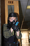 A woman police officer in training holding a paint ball simulated gun clearing a hallway in a school shooting scenario